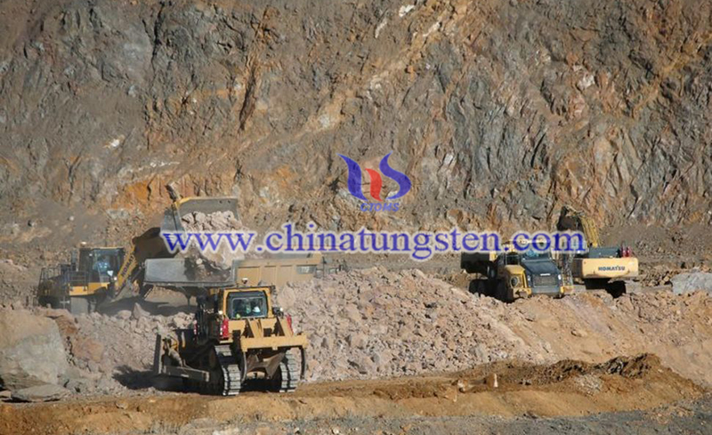 Wheel loaders fill trucks with ore at the MP Materials rare earth mine image